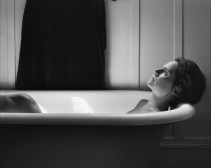 Black-and-white photograph of a woman reclining in a white bathtub looking up
