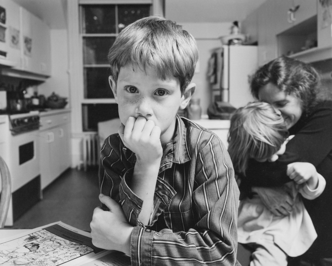 Black-and-white photograph of a boy seated in a kitchen with his chin in his hand with a woman and child behind him