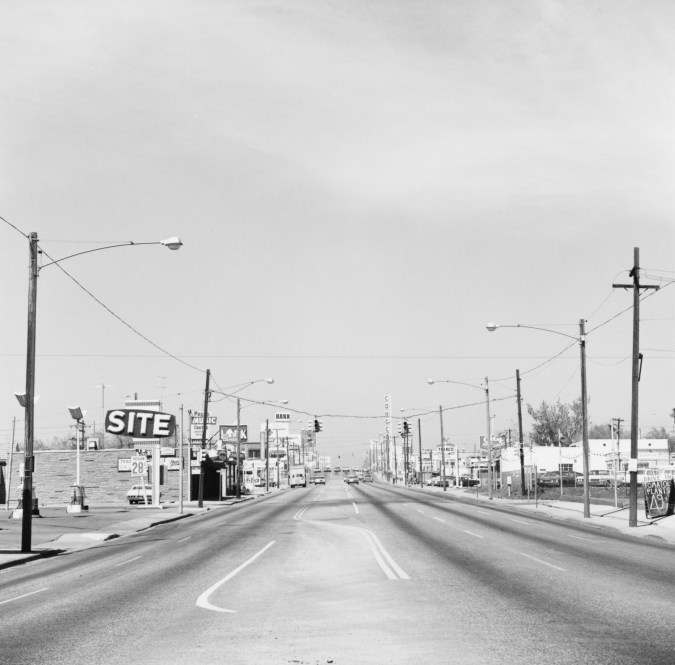 A black and white photograph of an empty street lined with businesses.