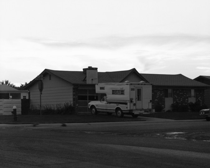 A black and white photograph of a pickup truck camper parked in the driveway of a suburban house.