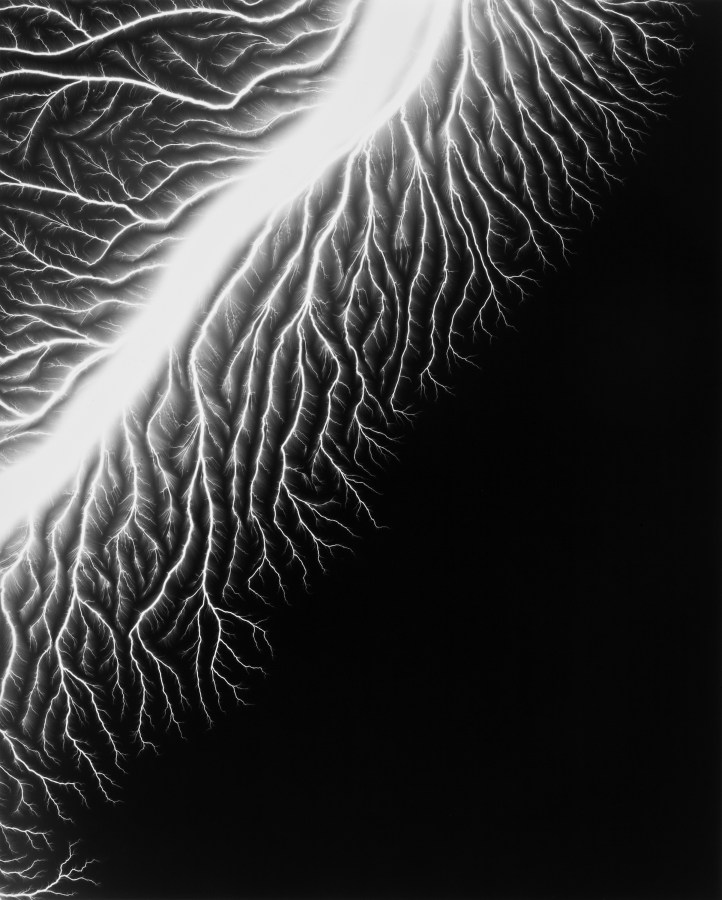 Black-and-white photograph of a white trail of light in the top left corner with smaller branches coming off of it on a black background