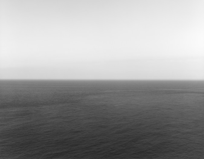 Black-and-white photograph of a rippled seascape with a bright white sky and dark gray sea