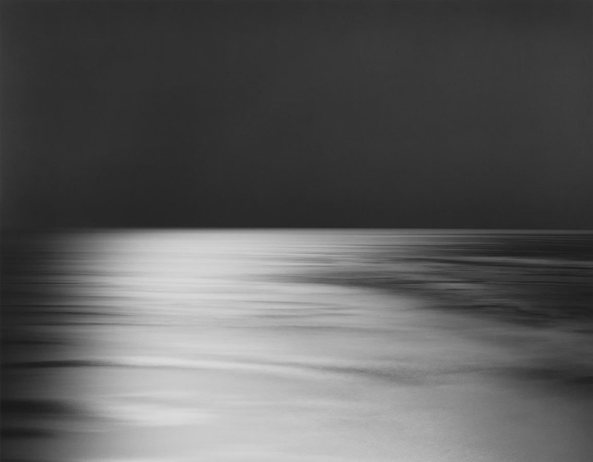 Black-and-white photograph of a seascape, with a black sky and a white light cast across an otherwise black sea