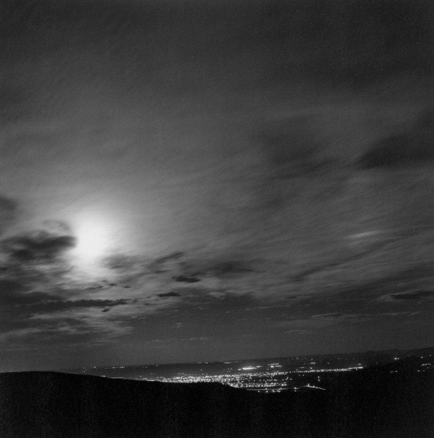 Black-and-white photograph of city lights in the distance at night