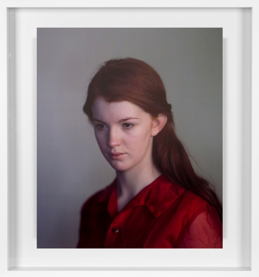 Color photographic portrait of a young woman with tied-back red hair and a red shirt on a gray background