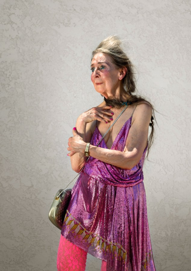 Color photographic portrait of an older woman in a pink sparkly top with her hand on her chest gazing off camera