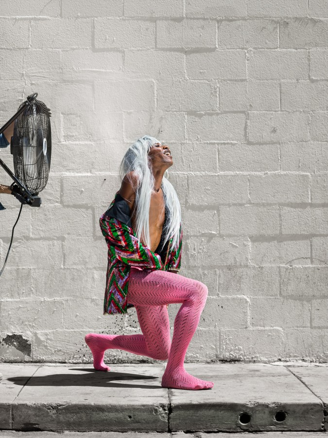 Color photograph of a woman in pink tights lunging in front of a fan and a cinderblock wall