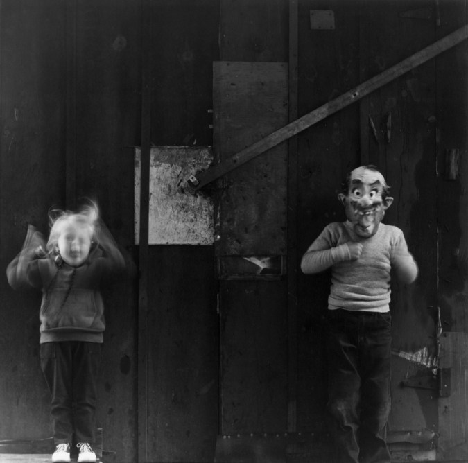 Black-and-white photograph of two children, one making a funny face and one in a Halloween mask.