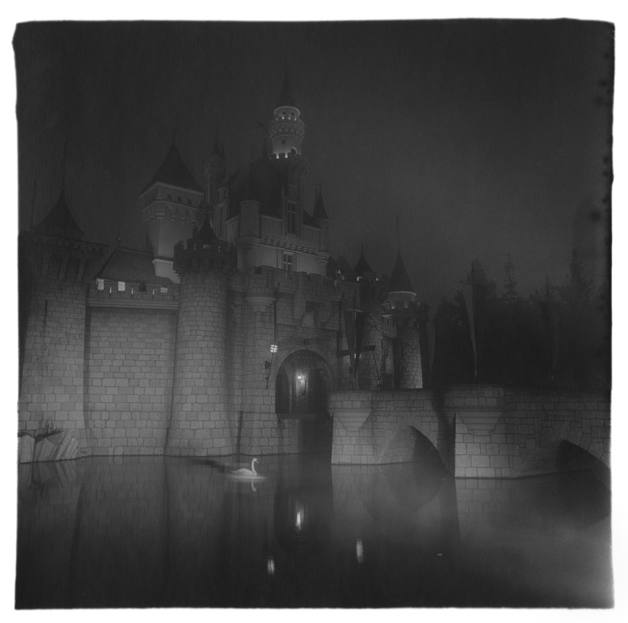 Black-and-white photograph of a dramatically lit castle at night with fog