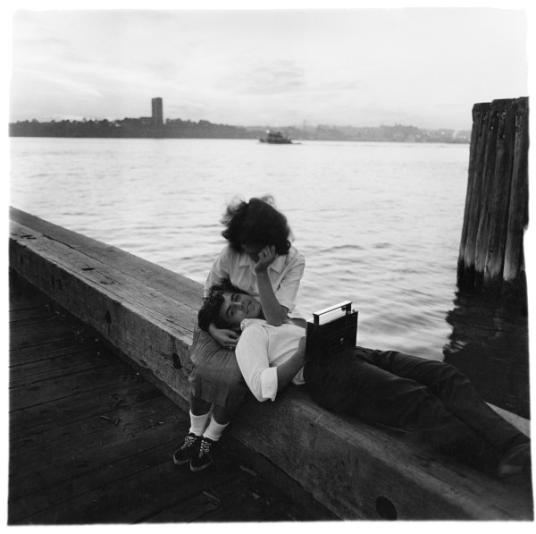 Black-and-white photograph of a woman sitting with man laying down resting his head on her lap with water in the background