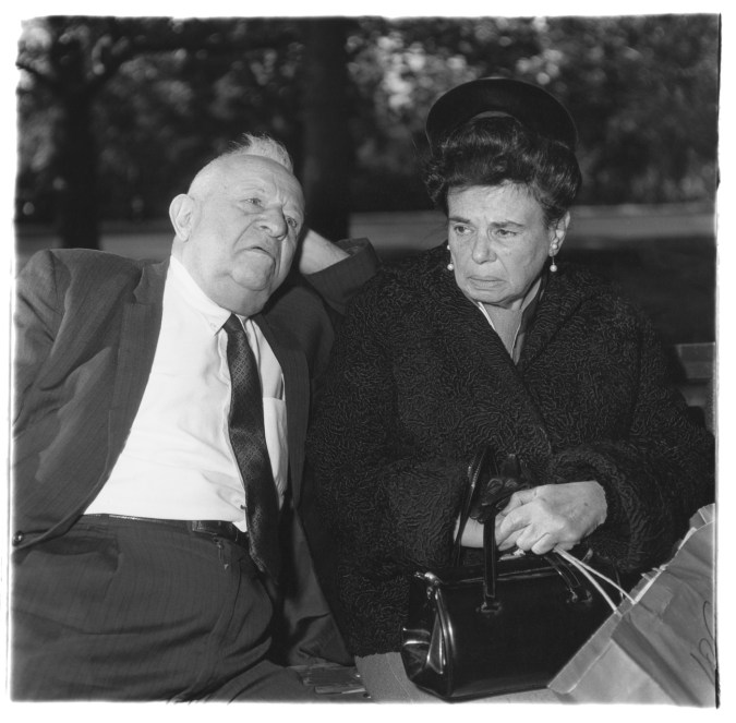 Black-and-white photograph of a man resting his head on his hand and a woman holding a purse and shopping bag