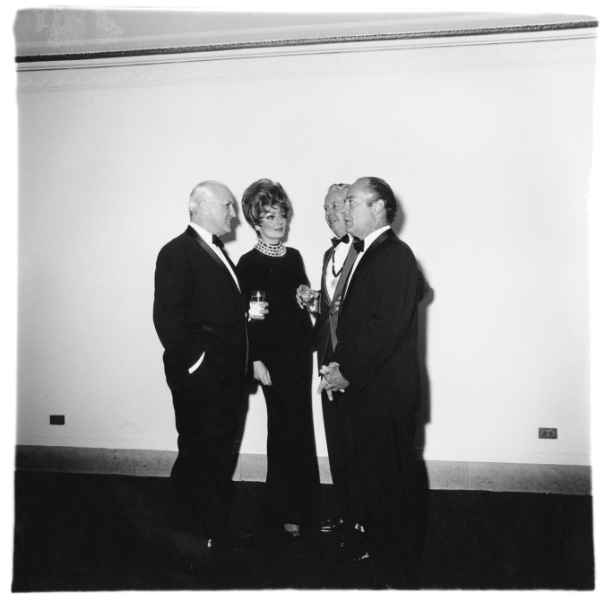 Black-and-white photograph of four figures wearing formal attire gathered in front of a white wall