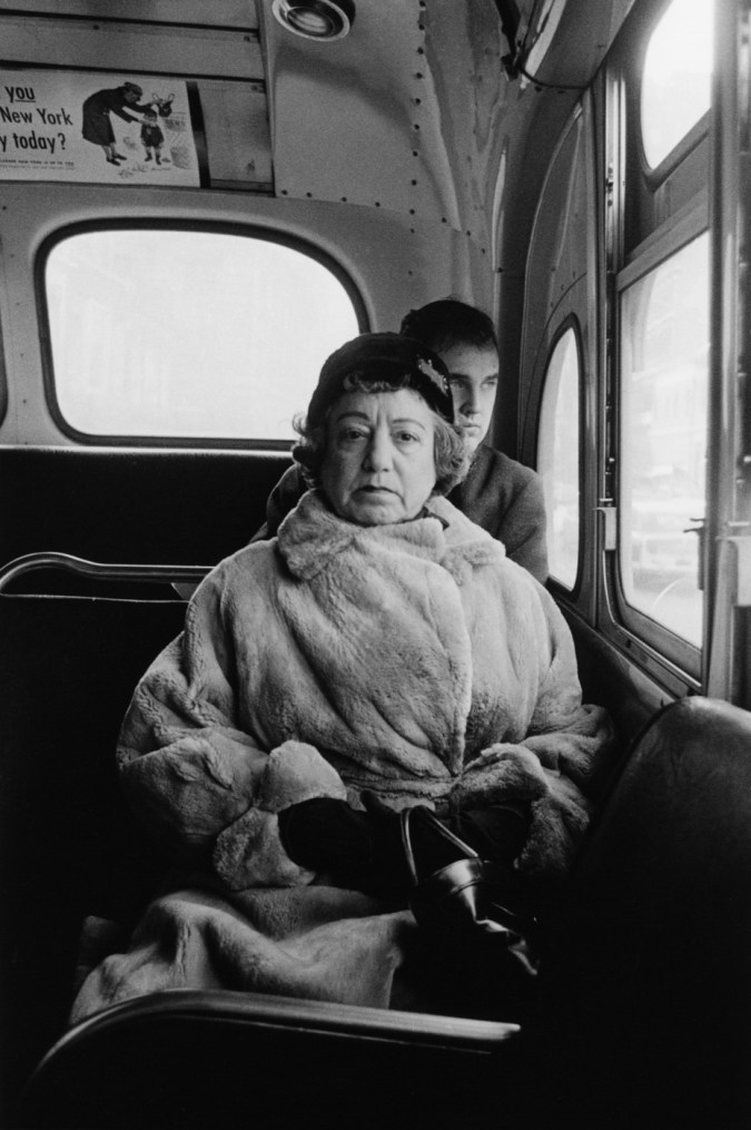 Black-and-white photograph of a woman wearing a fur coat and hat sitting in the back of a bus