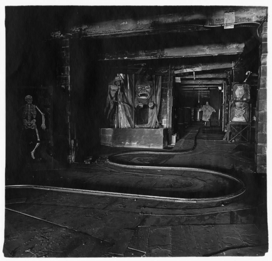 Black-and-white photograph with a track curving through the center, a skeleton on the right, and scary faces on the wall