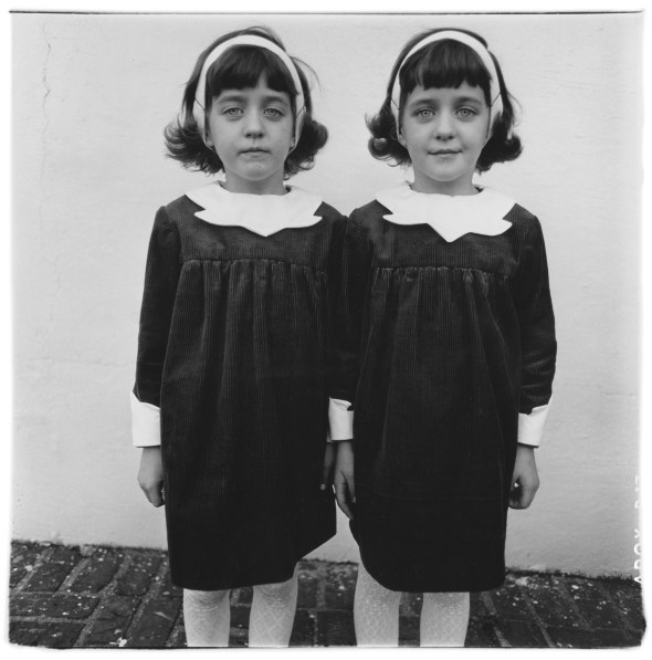 Black-and-white photograph of two girls in identical outfits against a white wall