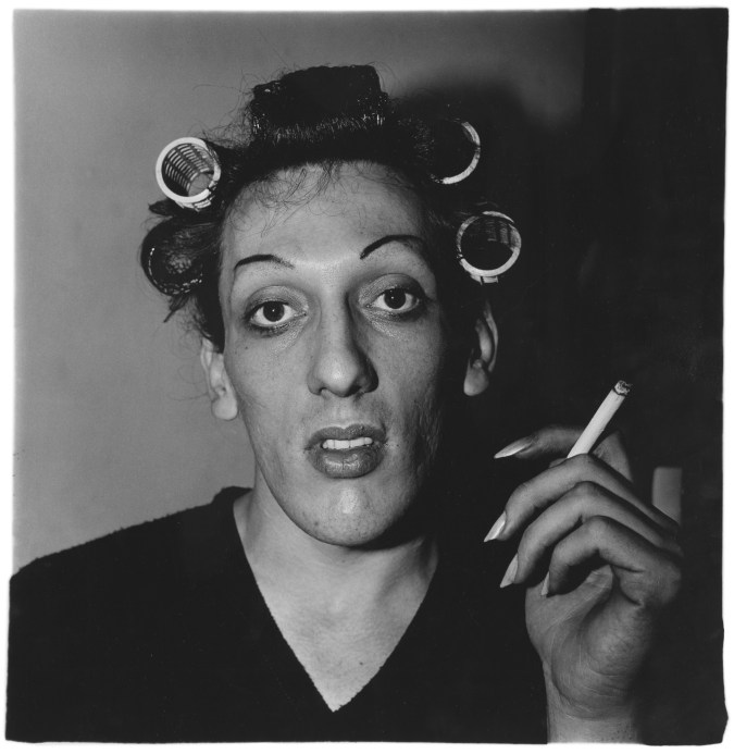 Black-and-white photograph a man with curlers in his hair holding a cigarette