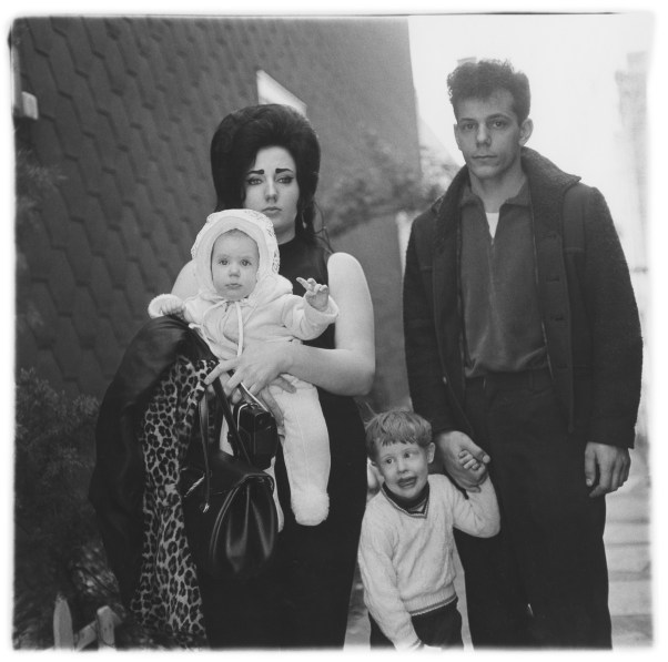 Black-and-white photograph of a woman holding a baby and a man holding the hand of a young boy