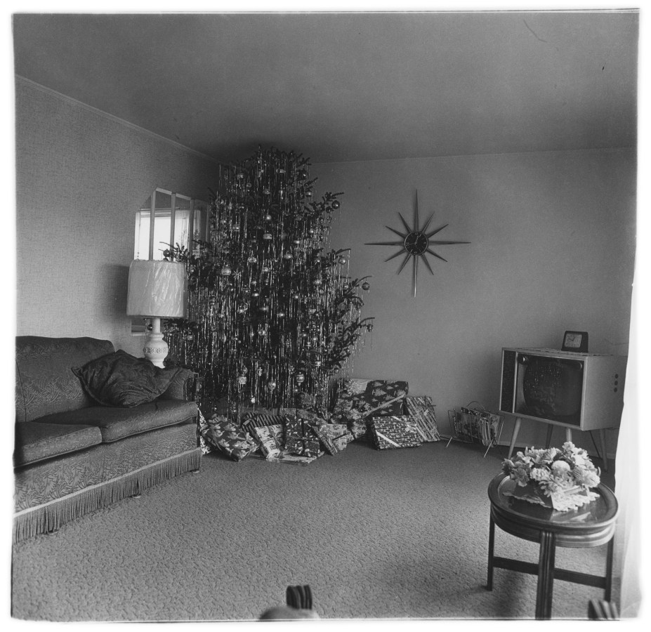 Black-and-white photograph of an empty living room with an oversized xmas tree with presents below