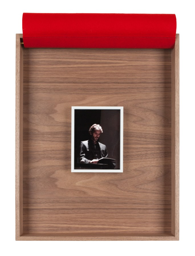 A framed photograph of a man in a suit, the bullfighter Jose Tomas, inside a wooden box