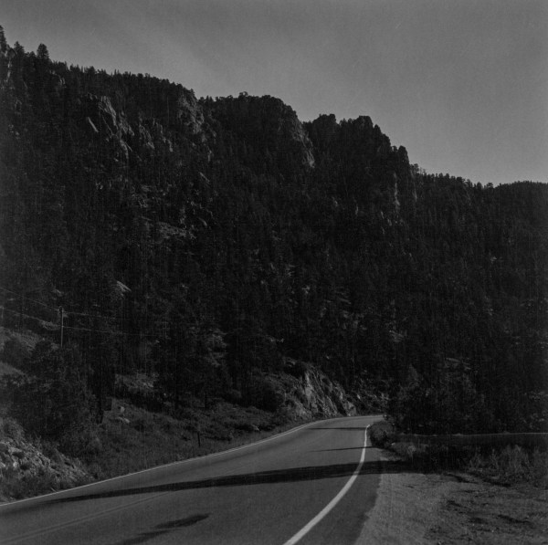 A black and white photograph of a road through a canyon at night
