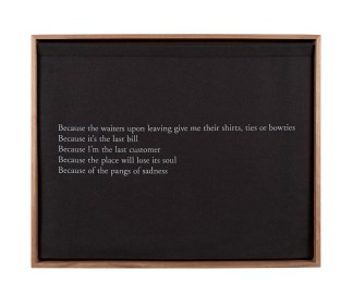 A wooden box with a black curtain, embroidered with white text, describing a restaurant