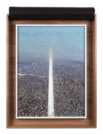 A framed photograph of a white line on the road receding into a pool of water, inside a wooden box