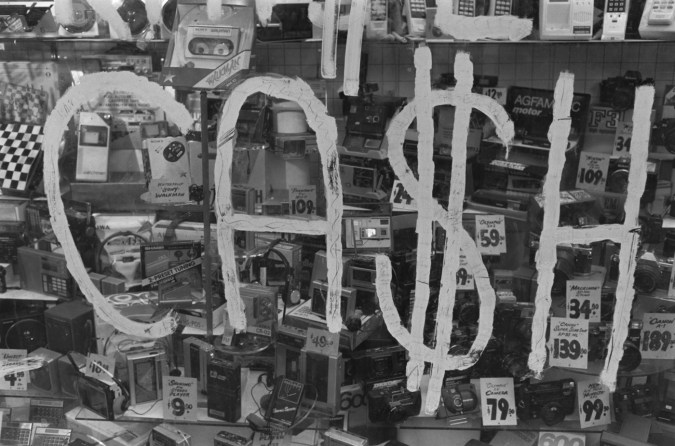 Black and white photograph of a sign that says cash with products in the background