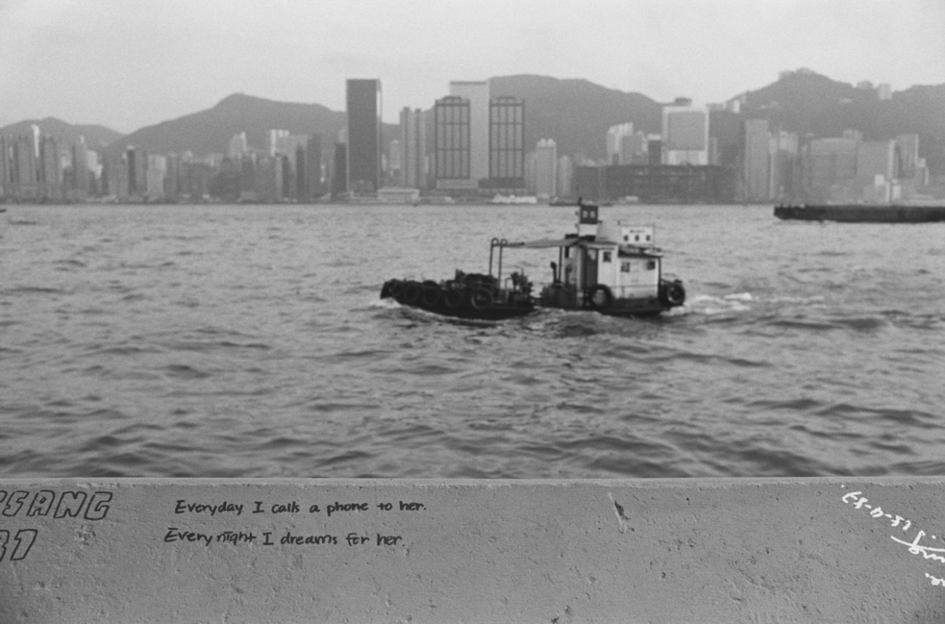 Black and white photograph with graffiti in the foreground a boat and a city skyline in the background
