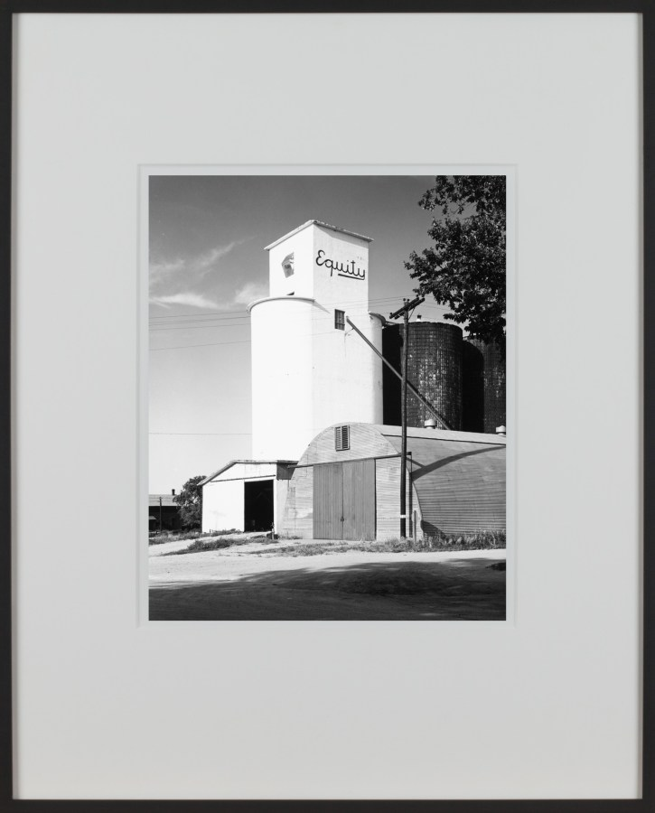 A framed vertical black and white photograph of a grain silo, with the word Equity painted at the top of the building