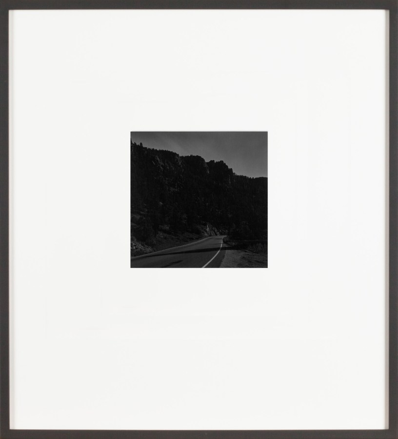 A framed black and white photograph of a road through a canyon at night
