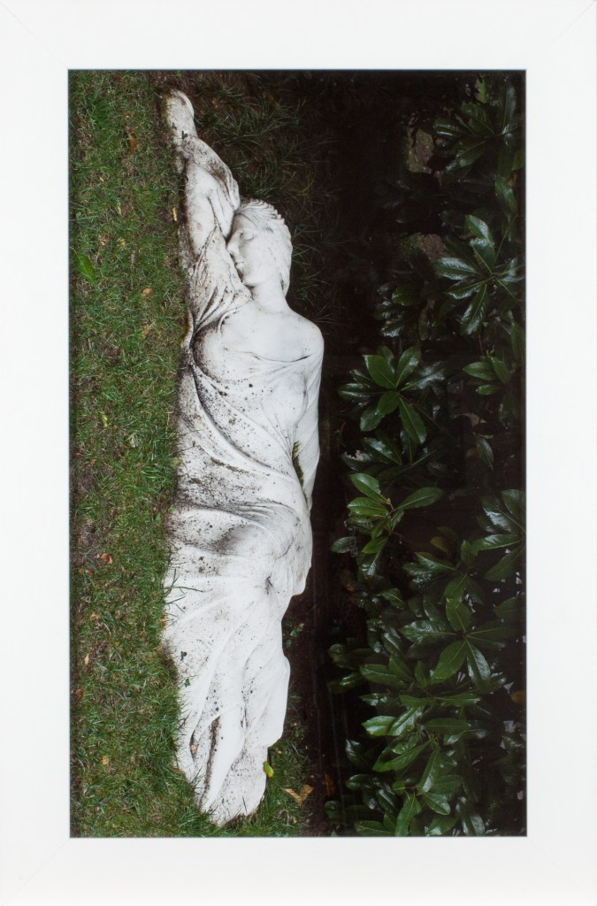 A framed photograph of a sculpture of a woman lying on her side, turned 90 degrees clockwise