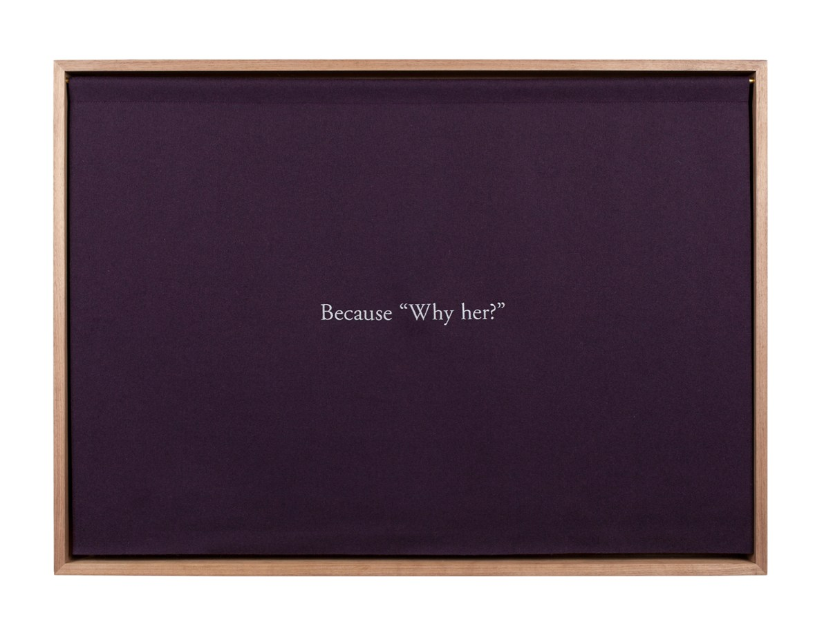 """A wooden box, with a purple curtain embroidered with white text, """"Because 'Why her?'"""""""