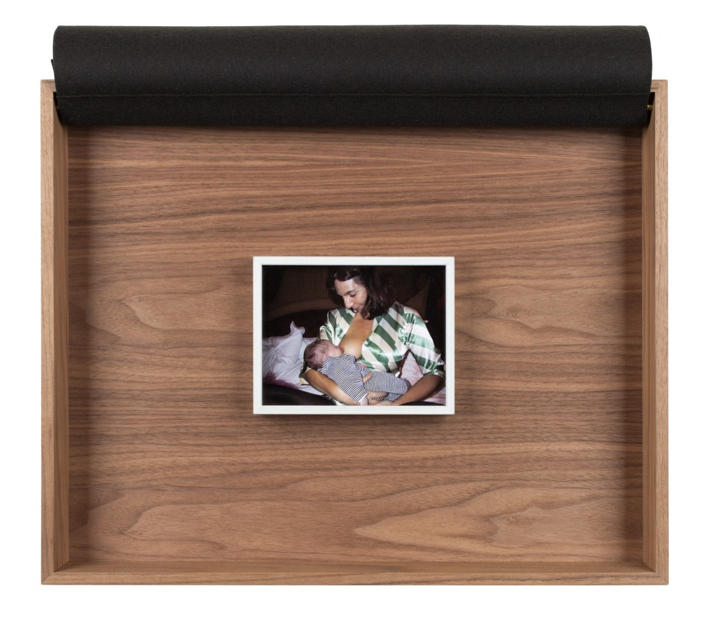 A framed photograph of the artist holding a child to her breast, inside a wooden box