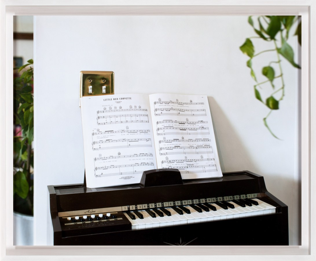 A framed photograph of an electronic organ, with sheet music turned to the song Little Red Corvette