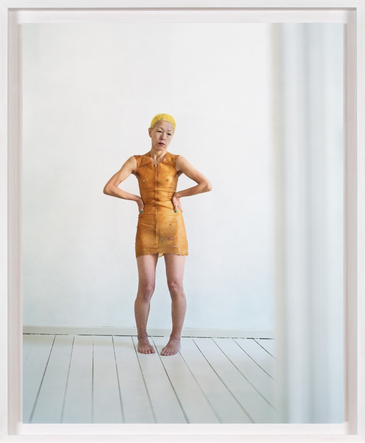 A framed photograph of a woman in a plain white room wearing an orange dress