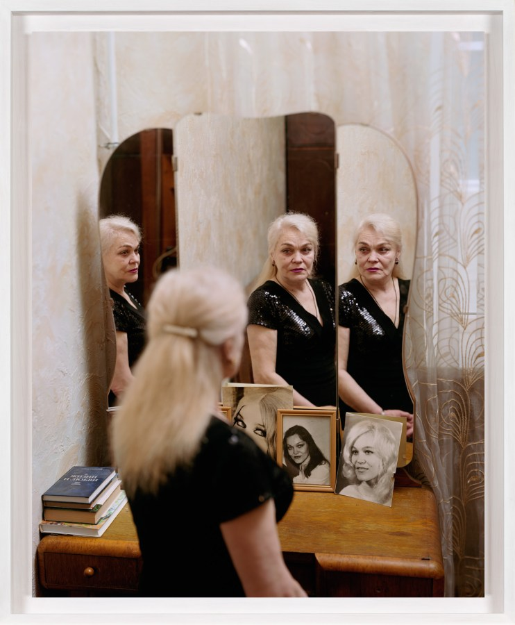 A framed photograph of an elderly woman looking at herself in the mirror, with three reflections