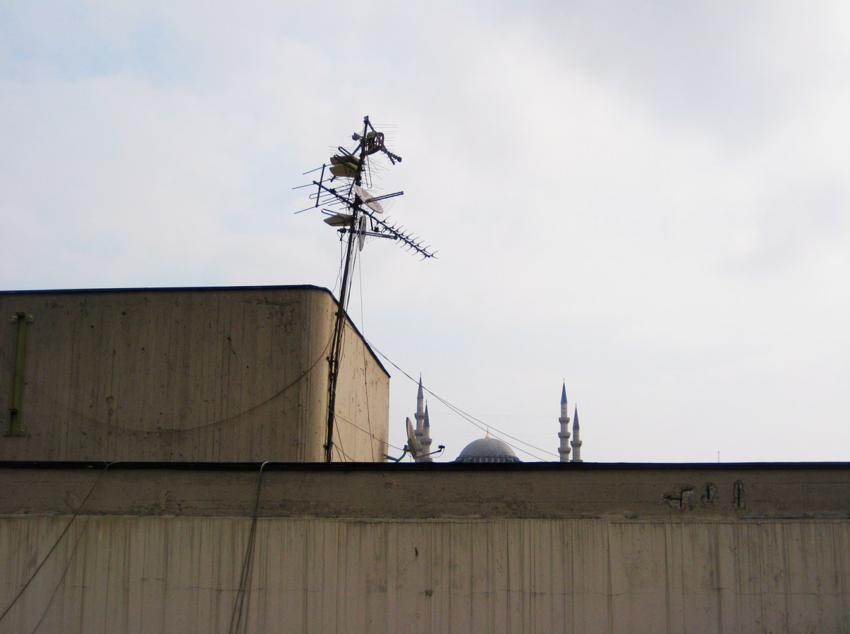 A color photograph of the top of a building, with speakers and satellite dishes on the roof. A mosque peeks out from the other side.