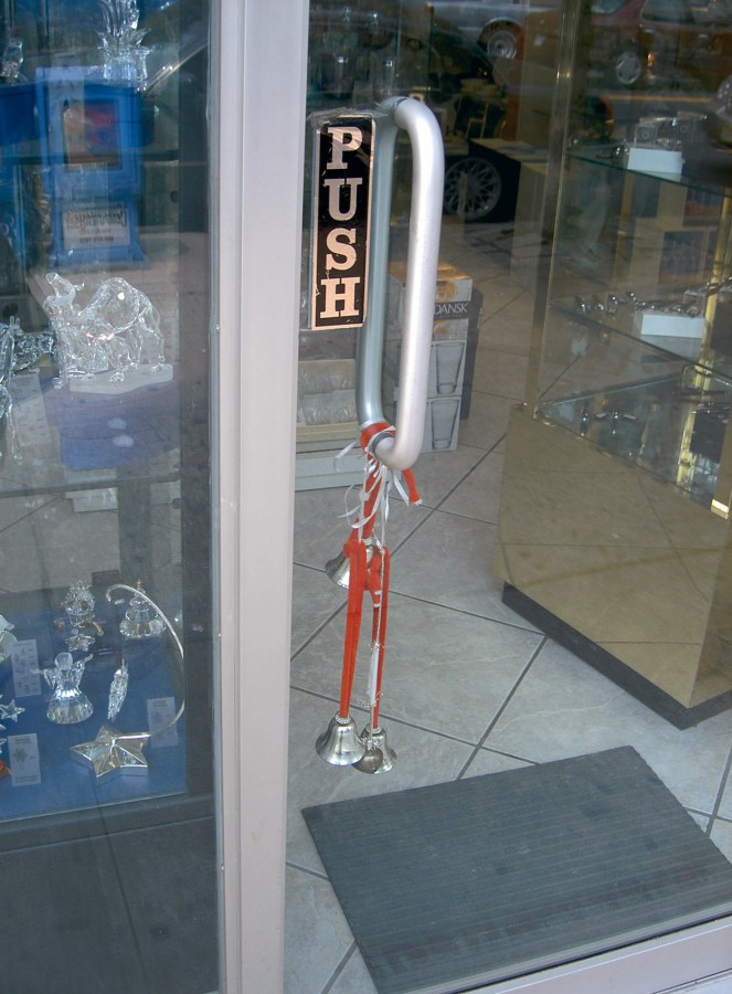 A color photograph of bells, strung on a red string, on a door handle of a store