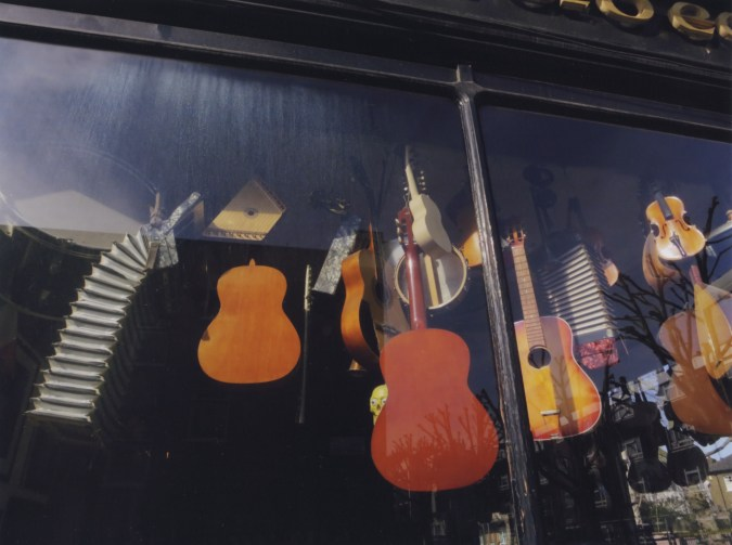 A color photograph of many musical instruments (mostly acoustic guitars), hanging in a storefront window