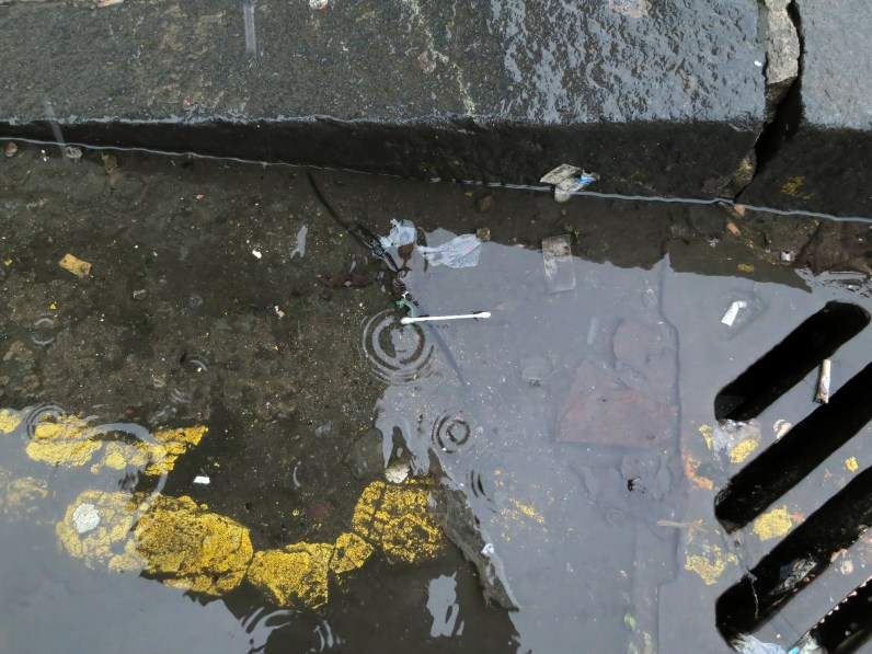 A photograph of a q-tip in a puddle on the side of the road, near the sidewalk curb.