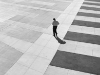 Black and white photograph of a lone man walking across an empty courtyard