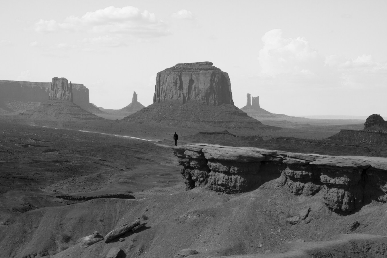 Black and white photograph of lone silhouetted figure in vast landscape of John Ford Point, in Monument Valley.