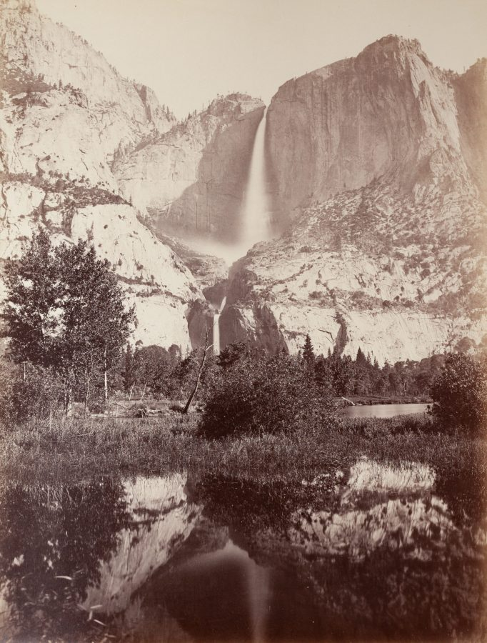 19th century photograph of cliffs and a waterfall, with water in the foreground reflecting the landscape