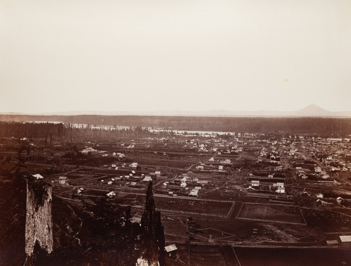 19th century photograph of faraway buildings and houses, with a river behind them, from an elevated vantage point