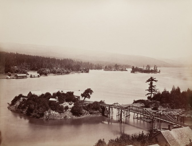Ninteteenth century photograph of a river with a bridge connecting to a small island in the middle of the river