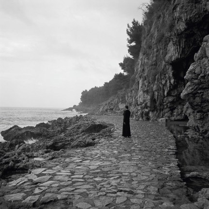 Black and white photograph of a person standing on a stone paved road next to a rocky coastline