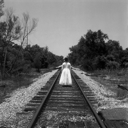 Black and white photograph of a woman in a spotted white dress with her back to the camera standing on railroad tracks