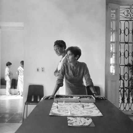 Black and white photograph of two women standing at a table with a board game and two children in the background