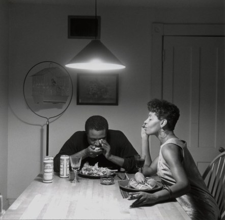 Black and white photograph of a kitchen table lit by an overhead lamp; an African American woman and man sit at the table, with plates of food.
