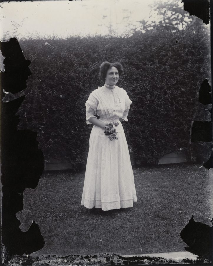 black and white photograph of a woman in a white dress standing outside in front of a hedge.